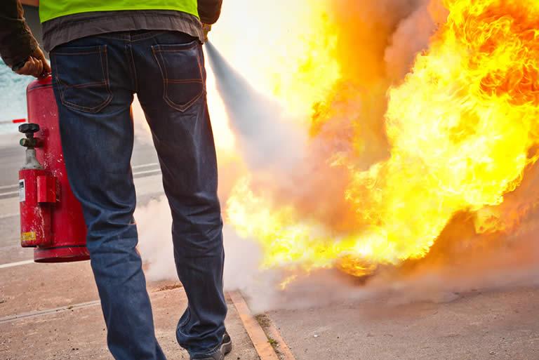 Homme maniant extincteurs pour éteindre incendie