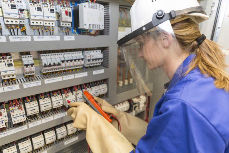 Femme travaillant devant tableau électrique. Habiltation